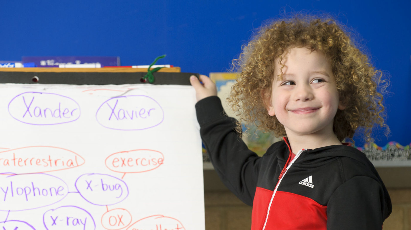 boy with curly hair smiling inside the room