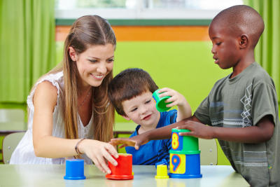 nursery teacher building tower with children in a kindergarten